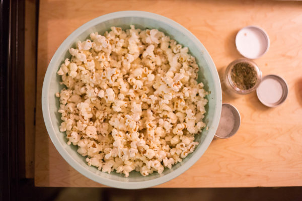 An overhead shot of a teal bowl of popcorn